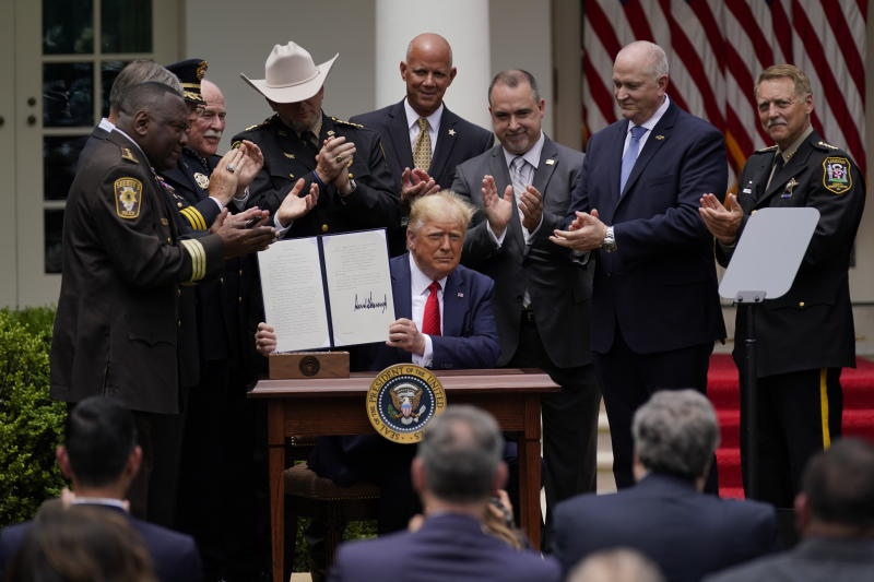 President Donald Trump holds up an executive order on police reform after signing it in the Rose Garden of the White House, Tuesday, June 16, 2020, in Washington. (AP Photo/Evan Vucci)