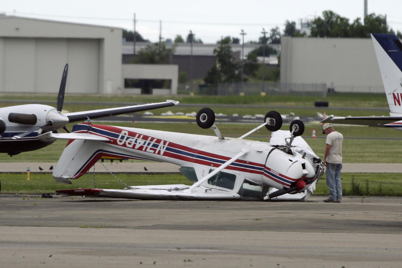 A man examines a small Cessna airplane that was flipped when strong winds struck in Jonesboro, Ark., Thursday, June 5, 2014. (AP Photo/Danny Johnston)