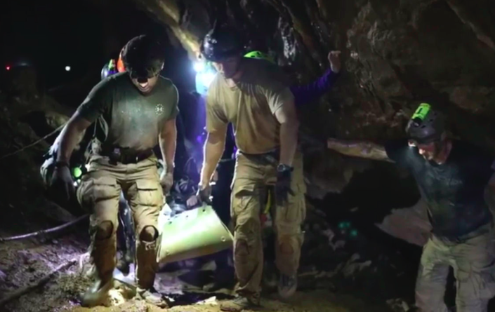 <em>Rescuers hold an evacuated boy inside the Tham Luang Nang Non cave in Mae Sai (AP)</em>