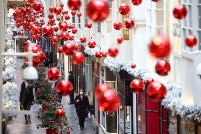 People walk through the Burlington Arcade adorned with Christmas decorations, in London
