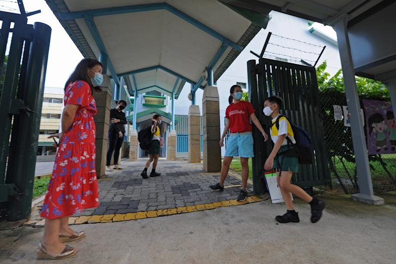 """SINGAPORE, June 2, 2020 -- Primary school students wearing face masks arrive at school in Singapore on June 2, 2020. Schools in Singapore reopened on Tuesday as the state embarked on a phased reopening from a COVID-19 """"circuit breaker"""" period to curb the spread of the coronavirus. (Photo by Then Chih Wey/Xinhua via Getty) (Xinhua/xinjiapo via Getty Images)"""