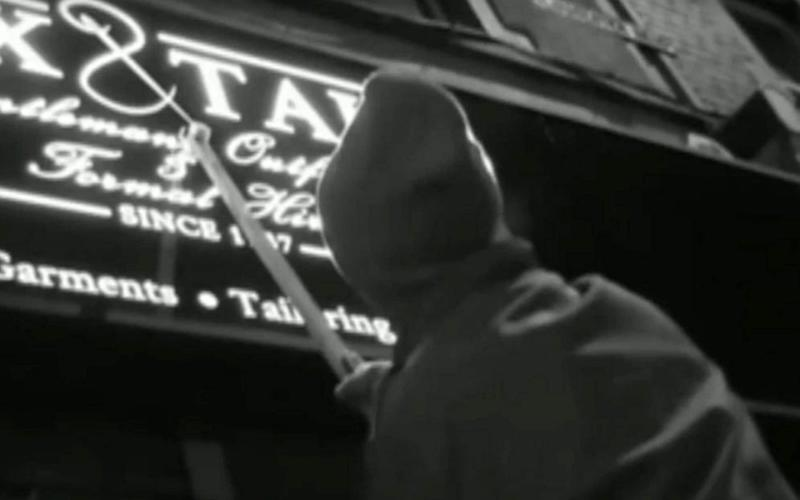 The anonymous crusader roams Bristol at night with the 'Apostrophiser' - a long-handled tool he created to reach the highest signs - BBC Points West / SWNS.com