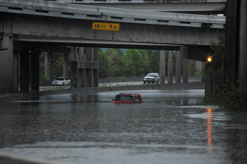 Floodwaters nearly cover an abandoned Hummer along Interstate 610 in Houston on Sunday. (Nick Oxford/Reuters)
