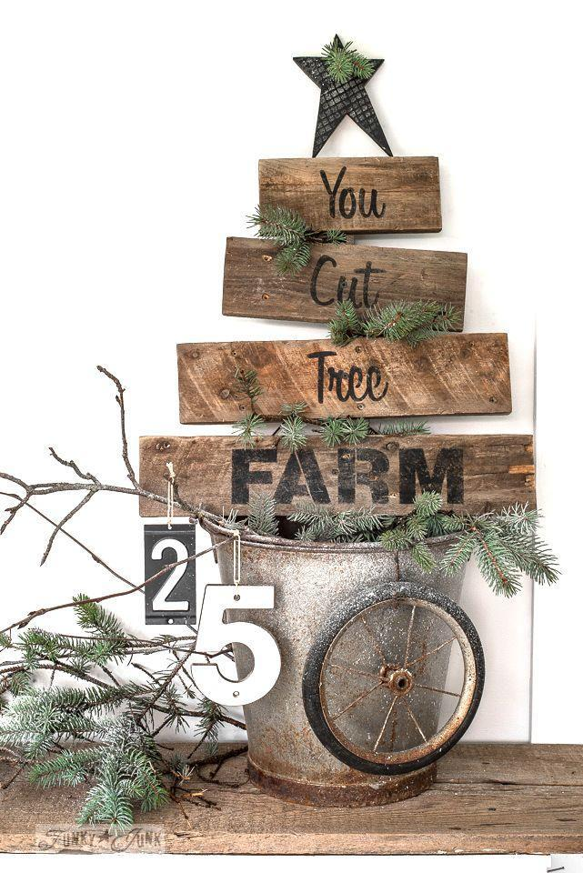 """<p>With its galvanized bucket stand and rustic star, this pallet Christmas tree and sign will fit right in at the farmhouse.</p><p><strong>Get the tutorial at <a href=""""https://www.funkyjunkinteriors.net/2017/11/pallet-wood-you-cut-tree-farm-christmas-sign.html"""" rel=""""nofollow noopener"""" target=""""_blank"""" data-ylk=""""slk:Funky Junk Interiors"""" class=""""link rapid-noclick-resp"""">Funky Junk Interiors</a>.</strong></p><p><strong><a class=""""link rapid-noclick-resp"""" href=""""https://www.amazon.com/Liquitex-BASICS-Acrylic-Paint-Black/dp/B0014ZNJVW/?tag=syn-yahoo-20&ascsubtag=%5Bartid%7C10050.g.23322271%5Bsrc%7Cyahoo-us"""" rel=""""nofollow noopener"""" target=""""_blank"""" data-ylk=""""slk:SHOP ACRYLIC PAINT"""">SHOP ACRYLIC PAINT</a><br></strong></p>"""