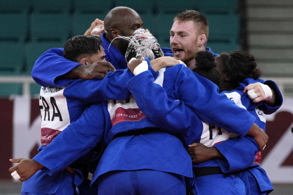 Members of the French team celebrate after defeating Japan in their gold medal match in team judo competition at the 2020 Summer Olympics, Saturday, July 31, 2021, in Tokyo, Japan. (AP Photo/Vincent Thian)