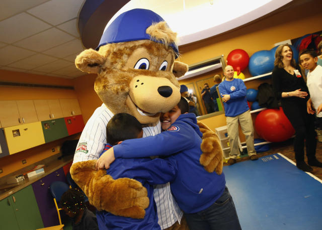 This Monday, Jan. 13, 2014 photo provided by the Chicago Cubs shows Clark, the team's first mascot, hugging children during his debut at Advocate Illinois Masonic's Pediatric Developmental Center in Chicago. Clark, a young bear wearing a Cubs jersey and backward blue baseball cap, is named after the North Side Chicago street on which Wrigley Field is located. (AP Photo/Courtesy of the Chicago Cubs, Steve Green)