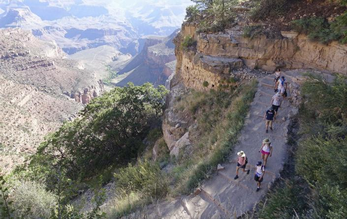 FILE - In this July 27, 2015, file photo, the busy Bright Angel Trail is crowded with hikers headed down into the Grand Canyon at Grand Canyon National Park, Ariz. The Interior Department is considering recommendations to modernize campgrounds within the National Park Service. (AP Photo/Ross D. Franklin, File)