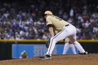 Arizona Diamondbacks relief pitcher Stefan Crichton pauses on the mound after giving up a run on a balk during the eighth inning of the team's baseball game against the Los Angeles Dodgers on Friday, June 18, 2021, in Phoenix. The Dodgers won 3-0. (AP Photo/Ross D. Franklin)