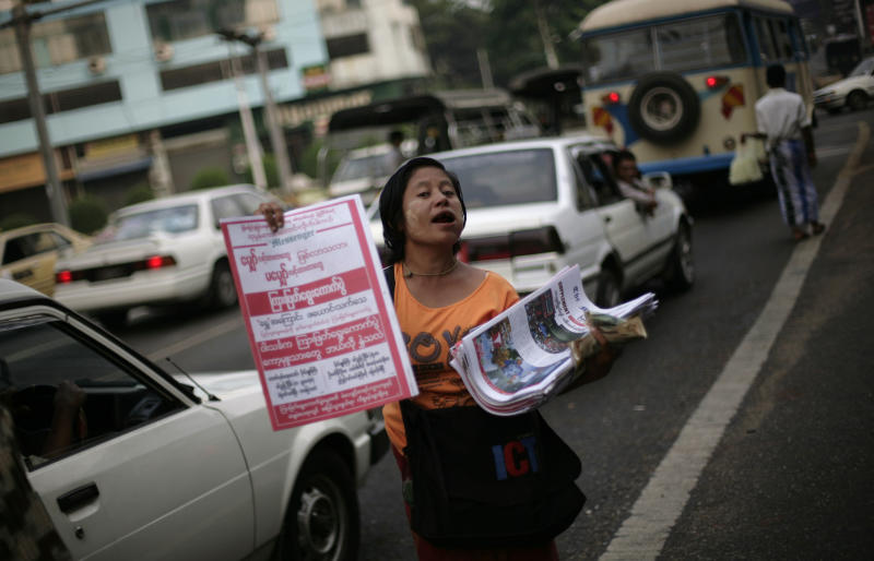 A Myanmar newspaper hawker sells newspapers at a traffic signal a day after landmark by-elections in Yangon, Myanmar, Monday, April 2, 2012. Myanmar's opposition icon Aung San Suu Kyi, 66, was elected to parliament Sunday in a historic victory buffeted by the jubilant cheers of supporters who hope her triumph will mark a major turning point in a nation still emerging from a ruthless era of military rule. (AP Photo/Altaf Qadri)
