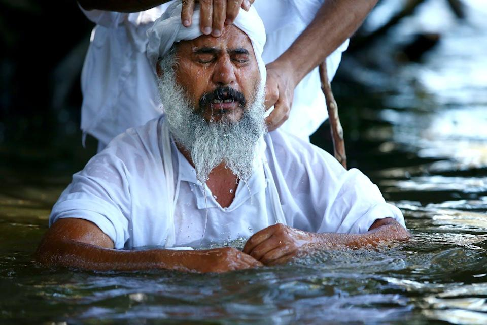 A follower being baptised during a Mandaean baptism ceremony in the Nepean river at Emu Plains on October 26, 2014 in Sydney, Australia.