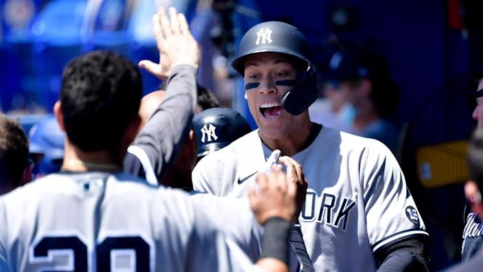 New York Yankees right fielder Aaron Judge (99) celebrates with teammates in the dugout after hitting a solo home run during the first inning against the Toronto Blue Jays at TD Ballpark.
