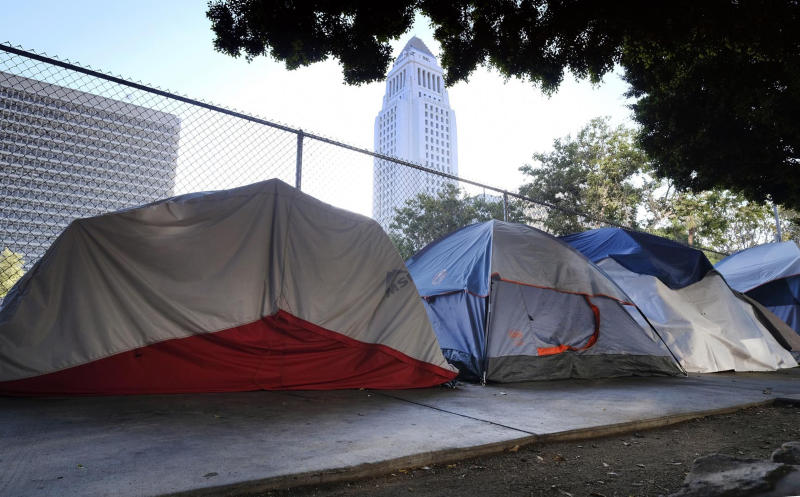 FILE - This Monday, July 1, 2019 file photo shows Los Angeles City Hall behind a homeless tent encampment along a street in downtown Los Angeles. Los Angeles Mayor Eric Garcetti says he hopes President Donald Trump will work with the city to end homelessness as the president visits California for a series of fundraisers. Garcetti says the federal government could aid Los Angeles with surplus property or money to create additional shelters. Garcetti says he has not been invited to meet with the president. (AP Photo/Richard Vogel, File)