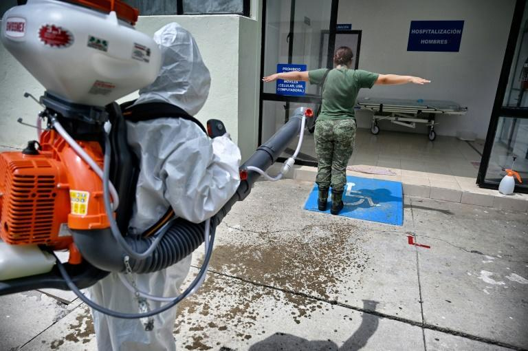 Erika Ramirez disinfects a colleague at a military hospital where she says she goes about her work with no fear