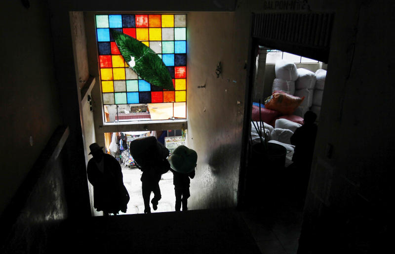 People enter a legal coca leaf market, some carrying bags of coca leaves, under a stained glass window decorated with an image of a coca leaf in La Paz, Bolivia, Friday, Jan. 11, 2013. President Evo Morales' global crusade to decriminalize the coca leaf, launched in 2006 after the coca growers' union leader was first elected president of Bolivia, has finally attained a partial, if largely, symbolic victory. A year ago, Bolivia temporarily withdrew from the 1961 U.N. convention on narcotic drugs because it classifies coca leaf, the raw material of cocaine, as an illicit drug. It has now rejoined, with one important caveat: The centuries-old Andean practice of chewing or otherwise ingesting coca leaves, a mild stimulant in its natural form, will now be universally recognized as legal within Bolivia. (AP Photo/Juan Karita)