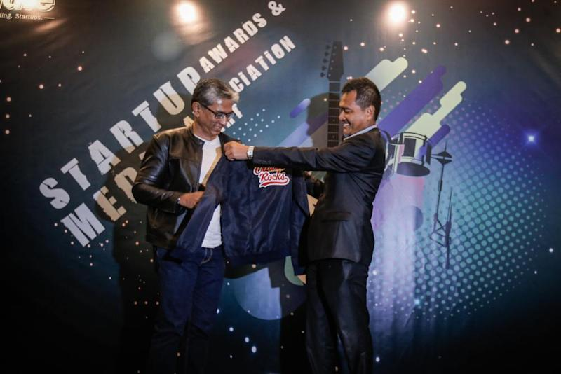 Dr Mohd Nor Azman Hassan receives a jacket from Cradle Fund Sdn Bhd Group CEO Razif Abdul Aziz during the first ever Cradle Startup Awards and Media Appreciation Night in Kuala Lumpur November 21, 2019. ― Picture by Hari Anggara