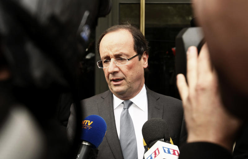 "French Socialist party candidate Francois Hollande, center, addresses journalists outside his apartment on the morning after the first round of the French presidential elections in Paris, France, Monday, April 23, 2012. Hollande has taken his plodding, undynamic campaign to become France's next president to within spitting distance of victory over the ""hyper-president"" Nicolas Sarkozy, finishing first in Sunday's initial round of voting. (AP Photo/Michel Spingler)"
