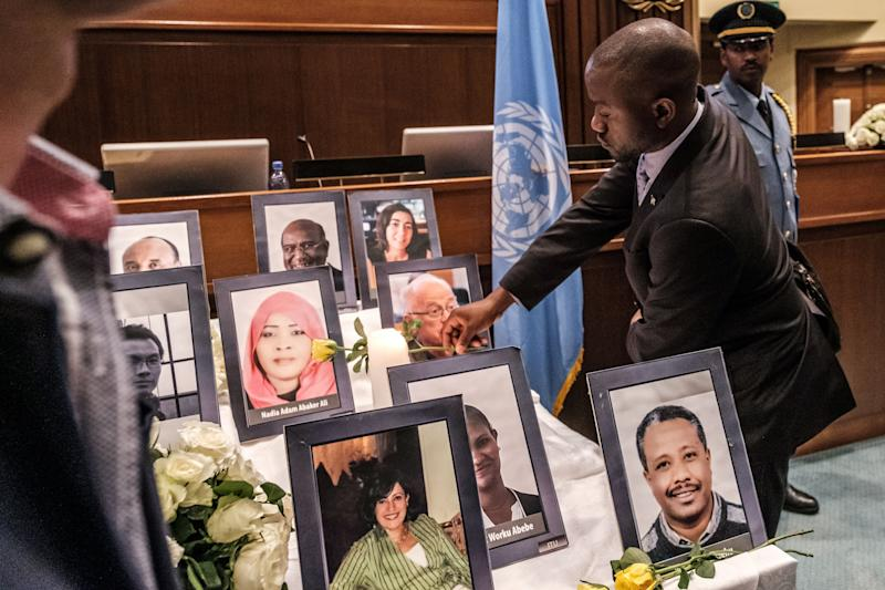 A man offers lays a flower at portraits of victims of the Ethiopian Airlines Boeing 737 MAX crash that killed 157 people one month prior hold flowers during a memorial service for UN and NGO personnel that died in the crash at the UN Economic Commission for Africa (UNCA) building in Addis Ababa, Ethiopia, on April 10, 2019. - Aviation regulators around the world grounded Boeing's 737 MAX last month following the Ethiopian Airways crash, which came less than five months after an October Lion Air crash that killed 189 people. (Photo by EDUARDO SOTERAS / AFP) (Photo credit should read EDUARDO SOTERAS/AFP/Getty Images)
