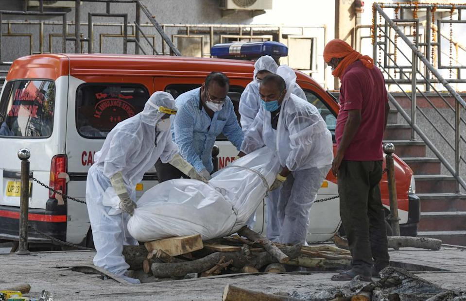 Relatives and medical workers in PPE overalls lay the body of a person who died of coronavirus on to a pyre at Nigambodh Ghat last week. Source: Getty