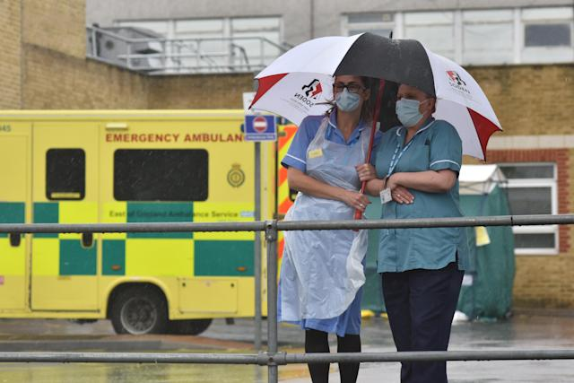 Two nurses stand under an umbrella during the pouring rain outside Southend Hospital during the minute's silence for key workers who have died. (Getty Images)