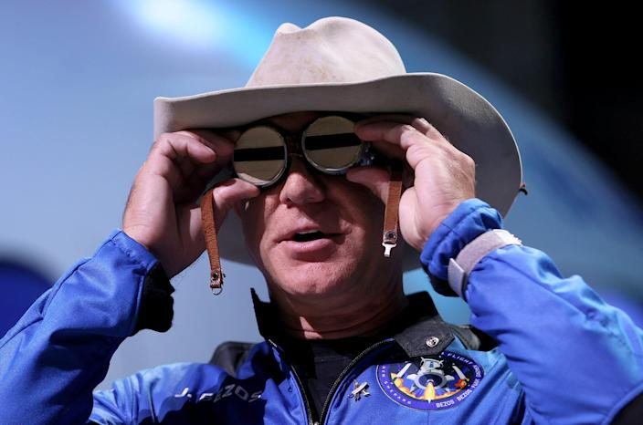 Blue Origin founder Jeff Bezos wears a pair of reflective aviation glasses under a cowboy hat