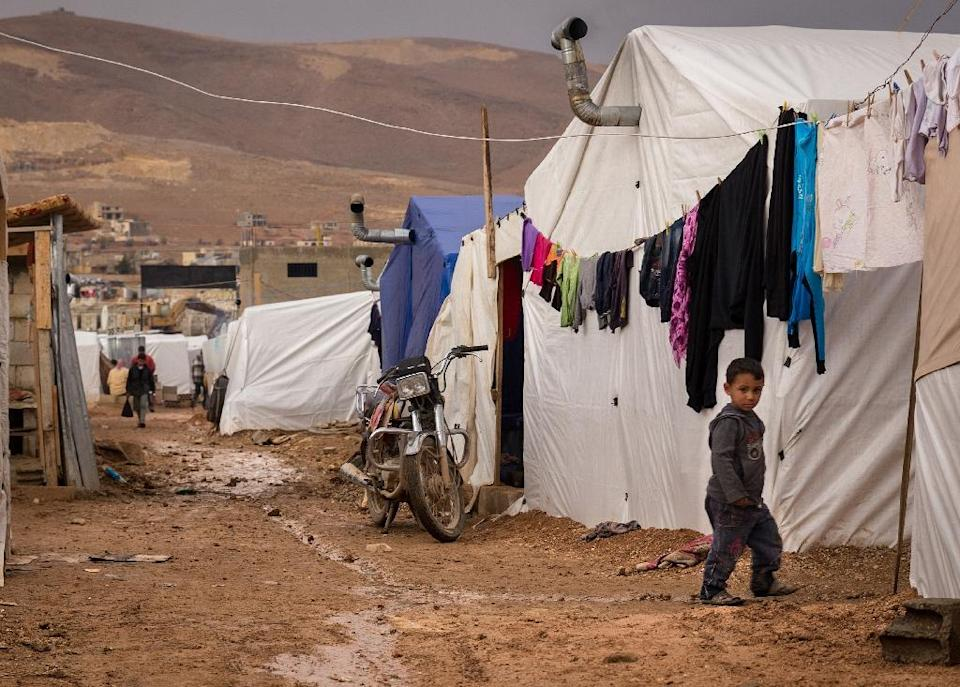 A young Syrian refugee walks past tents at the Al-Nihaya camp in the eastern Lebanese town of Arsal on October 23, 2014 (AFP Photo/Maya Hautefeuille)