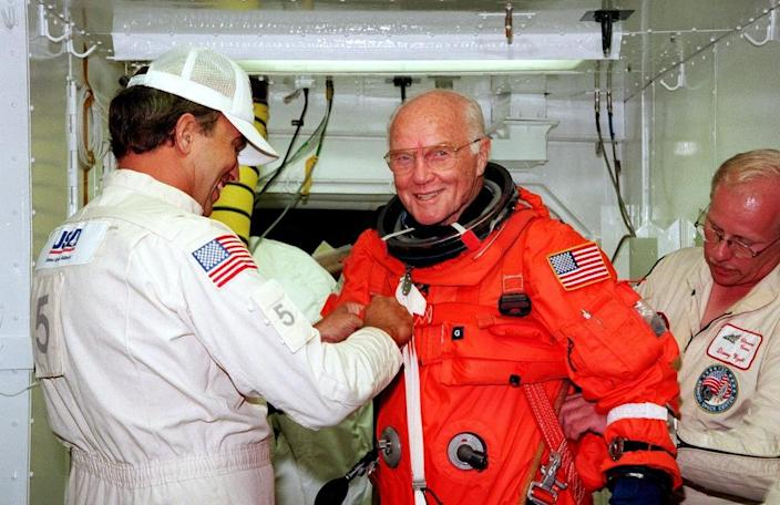 US astronaut and Senator John Glenn getting a hand from white room technicians moments before boarding the US space shuttle Discovery (AFP Photo/)