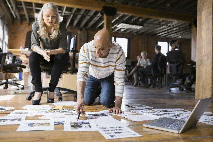 Business people look at proofs on the floor. (Getty Stock)