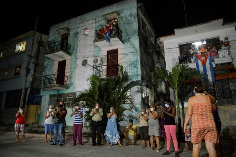 Neighbours applaud doctors and nurses who are battling the virus in Havana on March 30, 2020. Cuba is having trouble securing the medical supplies it needs to fight the pandemic (AFP Photo/Yamil LAGE)