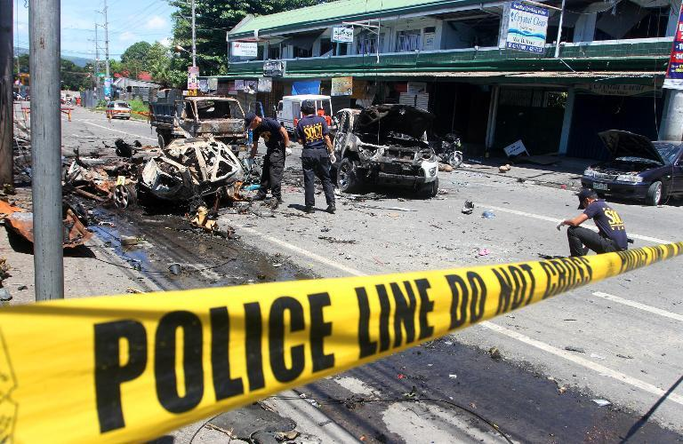 File photo of investigators looking for evidence among wreckage after a car bomb explosion in Cotabato city, on the southern island of Mindanao, on August 6 2013