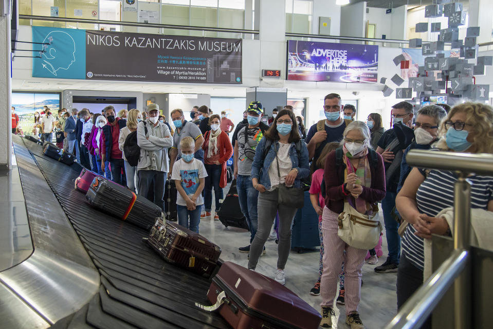 FILE - In this May 14, 2021, file photo, passengers from Hanover wait to pick their luggage at Nikos Kazantzakis International Airport in Heraklion, on the island of Crete, Greece. Coronavirus infections, hospitalizations and deaths are plummeting across much of Europe. Vaccination rates are accelerating, and with them, the promise of summer vacations. (AP Photo/Harry Nakos, File)
