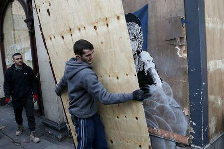 A worker carries a board to cover a new graffiti mural attributed to Banksy, opposite the French embassy in London, Britain January 25, 2016. REUTERS/Stefan Wermuth