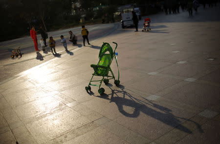 FILE PHOTO: A baby stroller is seen as mothers play with their children at a public area in downtown Shanghai November 19, 2013. REUTERS/Carlos Barria