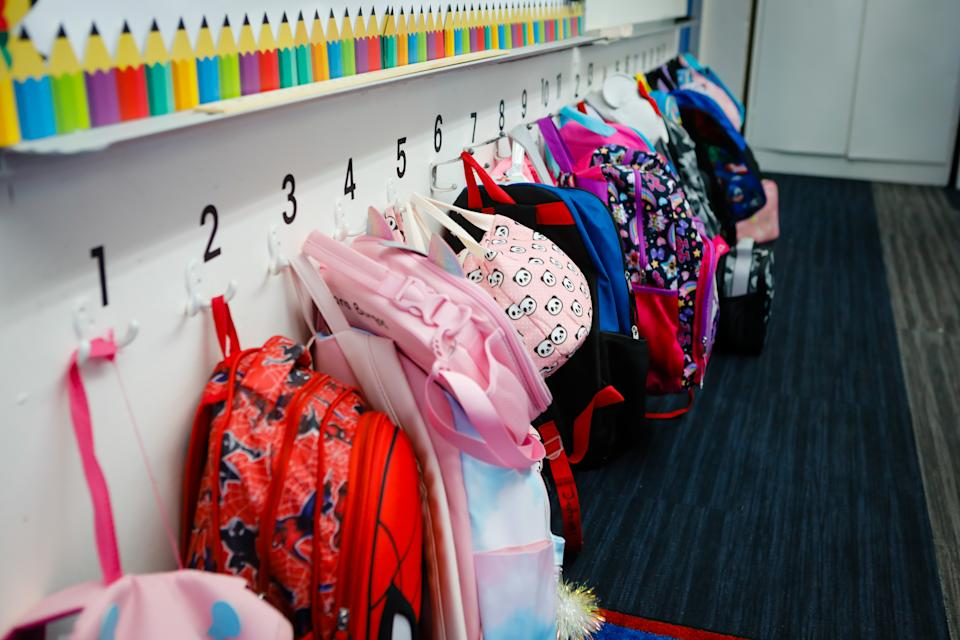 Student backpacks hang in a classroom during the first day of classes