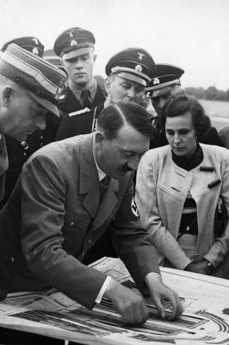 """<div class=""""inline-image__caption""""><p>Adolf Hitler checking plans for the forthcoming parades on the terrain of the Nuremberg rally and Leni Riefenstahl, at right, who was commissioned to shoot the official film about the rally, on Aug 20, 1934.</p></div> <div class=""""inline-image__credit"""">Heinrich Hoffmann/ullstein bild via Getty</div>"""