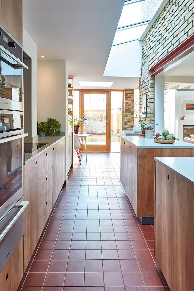 After: Warm wood cabinet fronts and gently speckled gray Corian countertops, both by Pluck, and dusty red traditional English quarry tiles are the perfect compliment to the kitchen's exposed brick wall.
