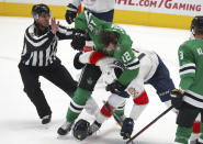 Lineman Ryan Galloway moves to break up a fight between Dallas Stars center Radek Faksa (12) and Florida Panthers left wing Mason Marchment (19) in the first period during an NHL hockey game on Sunday, March 28, 2021, in Dallas. (AP Photo/Richard W. Rodriguez)