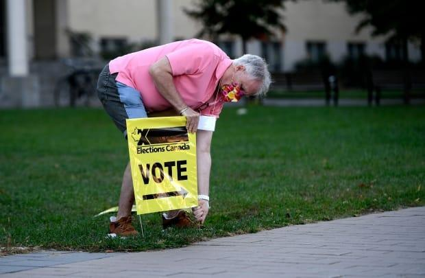 An Elections Canada officer plants a sign directing voters to a polling location in Ottawa on Sept. 20, 2021. (Justin Tang/Canadian Press - image credit)