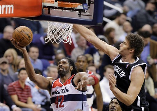 Washington Wizards center Nene (42), from Brazil, shoots as Brooklyn Nets center Brook Lopez (11) defends during the second half of an NBA basketball game Friday, Feb. 8, 2013 in Washington. Nene had 20 points as the Wizards won 89-74. (AP Photo/Alex Brandon)