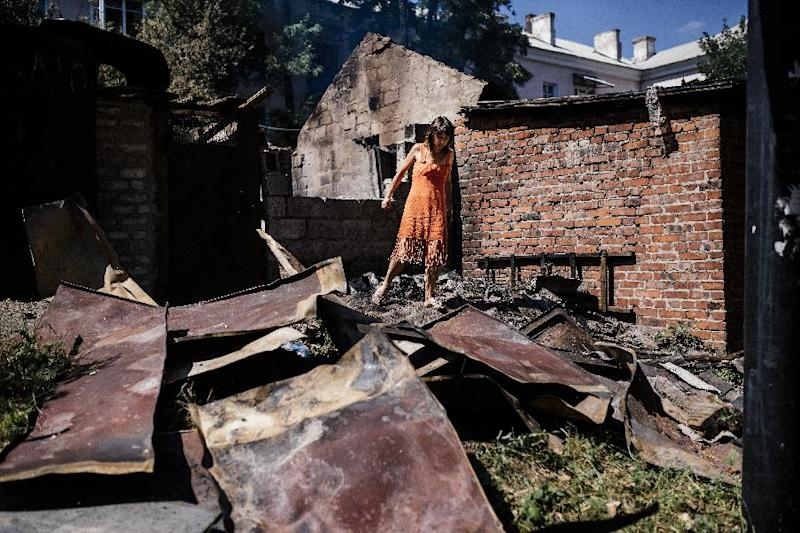 A woman walks through wreckage after shelling in Donetsk on August 9, 2014