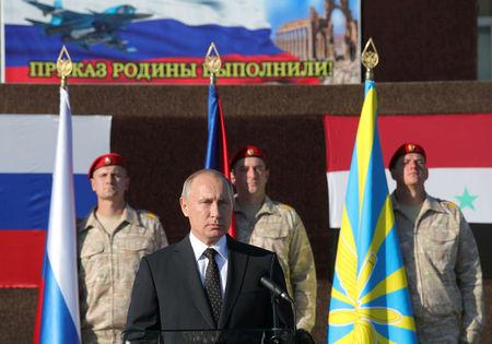 Russian President Putin addresses servicemen as he visits the Hmeymim air base in Latakia Province