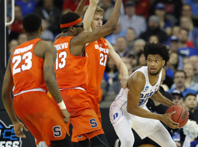 Duke's Marvin Bagley III, right, looks to pass around Syracuse's Frank Howard (23), Paschal Chukwu (13) and Marek Dolezaj (21) during the second half of a regional semifinal game in the NCAA men's college basketball tournament Friday, March 23, 2018, in Omaha, Neb. (AP Photo/Charlie Neibergall)