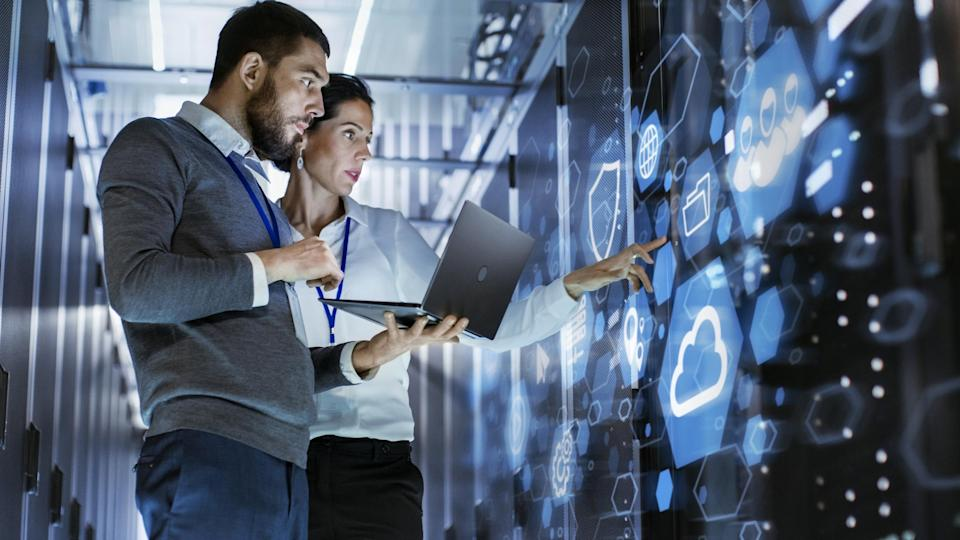 A man and woman standing in a server room, while the woman points at a wall of blue symbols for cloud and security features.