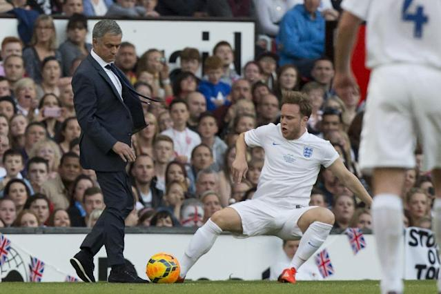 Singer Olly Murs, bottom right, playing for an England team is tripped up by Jose Mourinho manager of a Rest of the World team during the Soccer Aid 2014 charity soccer match at Old Trafford Stadium, Manchester, England, Sunday June 8, 2014. (AP Photo/Jon Super)