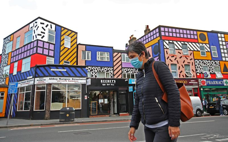 <strong>A woman wearing a face mask walks past shops and a mural created by artist Camille Walala, amid the spread of the coronavirus disease (COVID-19), in Leyton, London, Britain, September 29, 2020. REUTERS/Peter Cziborra</strong> (Photo: Peter Cziborra / Reuters)