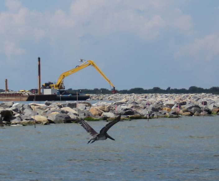A pelican flies past an excavator that is moving rocks to armor he edges of a Louisiana barrier island on Wednesday, July 28, 2021. Contractors are at work on a $102 million Louisiana Coastal Restoration and Protection Authority project to add about 400 acres of beach, dune and marshland to Grand Terre Island. Weather permitting, they hope to finish in November. (AP Photo/Janet McConnaughey)
