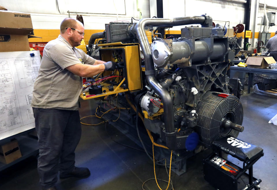 In this Sept. 18, 2019, photo technician David Boxx works on updating an electrical system on a Caterpillar machine at the Puckett Machinery Company in Flowood, Miss. On Tuesday, Oct. 1, the Institute for Supply Management, a trade group of purchasing managers, issues its index of manufacturing activity for September. (AP Photo/Rogelio V. Solis)