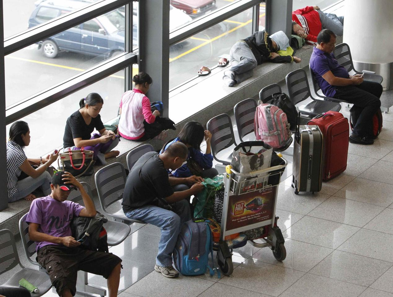 Stranded passengers wait at the lobby of Ninoy Aquino International airport in Pasay city, metro Manila November 8, 2013 after nearly 200 local flights have been suspended due to Typhoon Haiyan that hit central Philippines. Typhoon Haiyan, the strongest storm on earth this year, slammed into the Philippines' central islands on Friday forcing millions of people to move to safer ground and storm shelters, cutting power and phone lines, and grounding air and sea transport. The maximum category-five super typhoon, with destructive winds gusting of up to 275 kph (170 mph), whipped up giant waves as high as 4-5 meters (12-15 feet) that lashed the islands of Leyte and Samar, and was on track to hit holiday destinations REUTERS/Romeo Ranoco (PHILIPPINES - Tags: DISASTER ENVIRONMENT TRANSPORT)