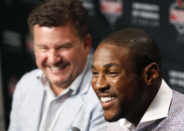 Arizona Cardinals' Patrick Peterson, right, smiles along with team president Michael Bidwill, left, announcing an agreement on a five-year, $70 million contract with $48 million guaranteed money with the football team during a news conference on Wednesday, July 30, 2014, in Glendale, Ariz. The agreement keeps Peterson under contract with Arizona through 2020. (AP Photo/Ross D. Franklin)