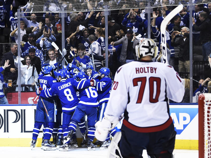 Washington Capitals goalie Braden Holtby (70) looks on as the Toronto Maple Leafs celebrate the game-winning goal during overtime in Game 3 of an NHL Stanley Cup first-round playoff series in Toronto on Monday, April 17, 2017. (Nathan Denette/The Canadian Press via AP)