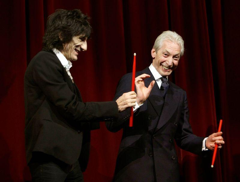 Rolling Stones Ron Wood and Charlie Watts (R) joke on the stage before the screening of their film 'Shine A Light' at the opening ceremony of the 58th Berlinale International Film Festival